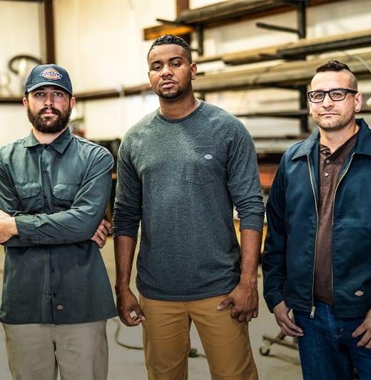 three men standing side by side in a workshop