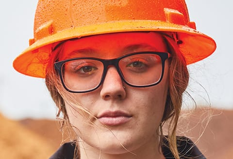close up image of a young woman wearing glasses and an orange hardhat